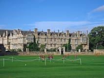 Engelska skolapojkar spelar en utomhus- sport liksom fotboll Arkivfoton