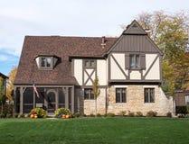 Engelska Tudor Home med amerikanska flaggan & pumpor Fotografering för Bildbyråer