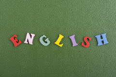 Engelska uttrycker på grön bakgrund som komponeras från träbokstäver för färgrikt abc-alfabetkvarter, kopieringsutrymme för annon Arkivbild