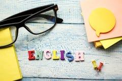 Engelska uttrycker samlat från träbokstäver för det färgrika abc-alfabetkvarteret, kopieringsutrymme för annonstext books isolera Royaltyfri Foto