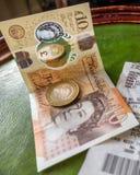Engelskt moneycoins och sedel och shoppakvitto royaltyfri foto