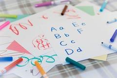 Engelskt; Ungar som skriver något engelskt alfabet för övning Royaltyfria Bilder