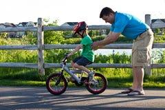 Engendre al hijo de enseñanza cómo montar una bici Imagen de archivo