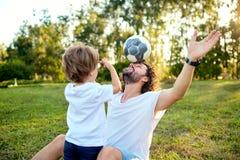 Engendre al hijo que juega con una bola en la hierba en el parque fotografía de archivo