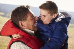Engendre al hijo que lleva al aire libre en el campo, cierre para arriba Foto de archivo