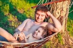 Engendre al papá que cosquillea al niño de la hija del niño en hamaca imagenes de archivo