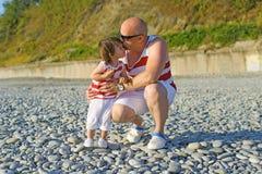 Engendre besar sus 2 años de hijo en ropa similar en la playa fotos de archivo