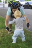 Engendre cercar a su bebé, niño que aprende caminar Foto de archivo libre de regalías