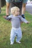 Engendre cercar a su bebé, niño que aprende caminar Imagen de archivo libre de regalías