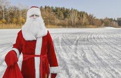 Engendre a Christmas, Santa Claus está en el bosque con un bolso de regalos foto de archivo