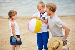 Engendre con dos niños en la playa en verano Foto de archivo