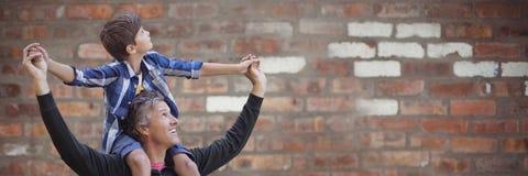 Engendre con el hijo en hombros contra la pared de ladrillo roja borrosa Imagen de archivo