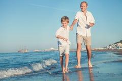 Engendre con el hijo que corre junto en la línea de la resaca del mar Imagen de archivo libre de regalías