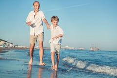 Engendre con el hijo que corre junto en la línea de la resaca del mar Foto de archivo