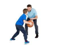 Engendre con el hijo que juega al baloncesto aislado en blanco Imágenes de archivo libres de regalías