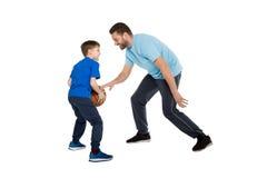 Engendre con el hijo que juega al baloncesto aislado en blanco Fotografía de archivo