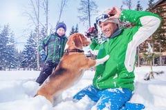 Engendre con el hijo que juega con su perro en nieve profunda Foto de archivo
