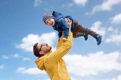 Engendre con el hijo que juega y que se divierte al aire libre imagenes de archivo