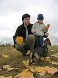Engendre con el hijo y el perro en las hojas de otoño Fotos de archivo libres de regalías