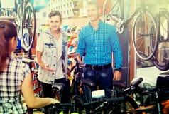 Engendre con el hijo y el vendedor de sexo femenino en tienda de la bici Foto de archivo