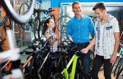 Engendre con el hijo y el vendedor de sexo femenino en tienda de la bici Fotografía de archivo