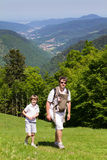 Engendre con el hijo y la hija recién nacida en un portador de bebé que camina en las montañas Imagen de archivo libre de regalías