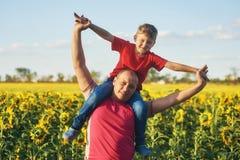 Engendre con el niño en un campo de girasoles florecientes Imagenes de archivo