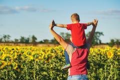 Engendre con el niño en un campo de girasoles florecientes Foto de archivo libre de regalías