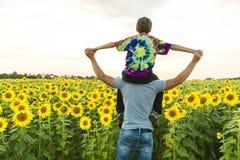 Engendre con el niño en un campo de girasoles florecientes, día del ` s del padre Foto de archivo