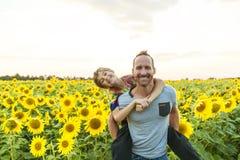 Engendre con el niño en un campo de girasoles florecientes, día del ` s del padre Imagen de archivo