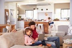 Engendre con el ordenador con el hijo, familia en fondo Foto de archivo libre de regalías