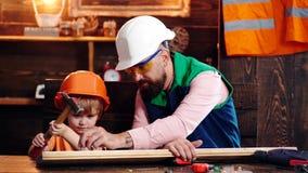 Engendre con la barba que enseña al pequeño hijo a utilizar las herramientas Muchacho, niño en casco protector que aprende utiliz metrajes