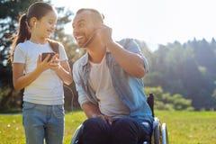 Engendre con la debilitación de la movilidad que escucha la música con la hija imagen de archivo