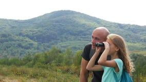 Engendre con la hija en las montañas que miran en la distancia almacen de video