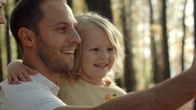 Engendre con la hija que toma el selfie con el teléfono en parque del otoño Fotografía de archivo libre de regalías