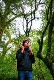 Engendre con la pequeña hija en sus hombros que miran para arriba la cascada, parque nacional de Westland, Nueva Zelanda Imagenes de archivo
