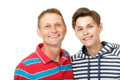 Engendre con la sonrisa feliz adolescente del hijo sobre blanco Fotografía de archivo libre de regalías