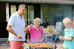 Engendre con los hijos que asan a la parrilla la carne en el jardín Imagen de archivo