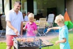 Engendre con los hijos que asan a la parrilla la carne en el jardín Foto de archivo