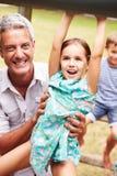 Engendre con los niños que se divierten en un patio Imagen de archivo
