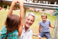 Engendre con los niños que se divierten en un patio Imagenes de archivo