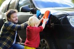 Engendre con su coche que se lava del hijo del niño junto Fotos de archivo