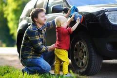 Engendre con su coche que se lava del hijo del niño junto Imagen de archivo libre de regalías
