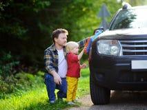 Engendre con su coche que se lava del hijo del niño junto Foto de archivo