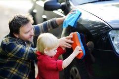 Engendre con su coche que se lava del hijo del niño junto Fotografía de archivo