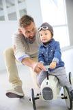 Engendre con su hijo en un juguete retro del coche Imagenes de archivo