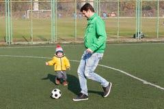 Engendre con su pequeño hijo que juega al fútbol, fútbol en el parque Imagen de archivo libre de regalías