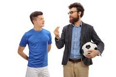 Engendre con un fútbol que explica algo a su hijo adolescente Imagen de archivo libre de regalías