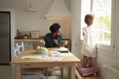 Engendre a And Daughter Paint y coma la pizza en la tabla de cocina Fotografía de archivo libre de regalías