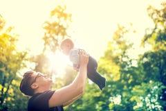 Engendre detener al niño en los brazos, lanzando al bebé en aire concepto de familia feliz, efecto del vintage contra luz Foto de archivo